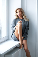 Young beautiful blonde is sitting on window in gray sweater