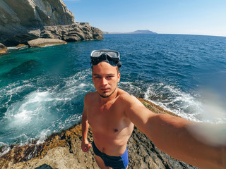 selfie sports men diver in the mask standing on the shore of the sea in swimming trunks