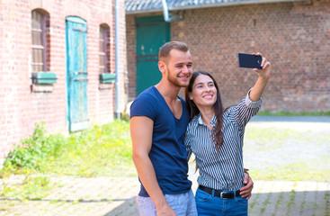 Outdoor portrait of romantic young couple taking selfie