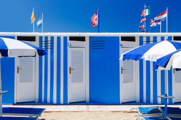 Colorful beach huts on summer day with blue sky. Flags on background.