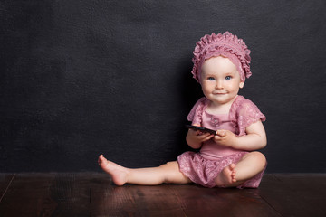 The girl sits on a brown floor and holds phone. The girl looks in the camera and smilles. Black background.