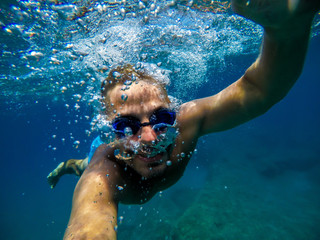 Underwater view of a young diver man swimming and enjoying at the sea for summer vacation while taking a selfie.