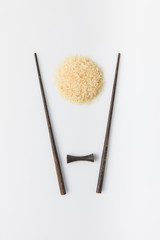 top view of raw rice with chopsticks isolated on white