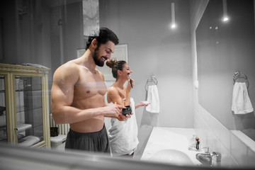 Young gorgeous attractive girl with towel standing in the bathroom with her shirtless muscular handsome boyfriend or husband and preparing their skin and hair together in front of mirror.