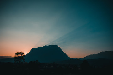 The sunset and sunlight behind a big mountain with clear sky in the evening