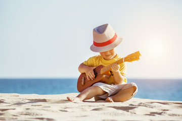 Guitar ukulele concept with little boy at the beach