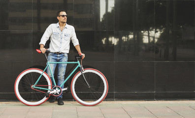 8daa984e5b A young stylish man with sunglasses posing next to his bicycle.