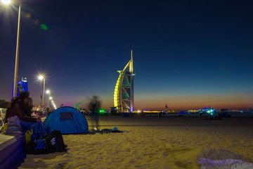 People waiting for new year celebration at the beach in last day of the year. The world's first seven stars luxury hotel Burj Al Arab and Dubai Marina in background
