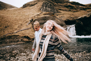 Iceland couple wearing Icelandic sweaters in beautiful nature landscape on Iceland. Woman and man model in typical Icelandic sweater.