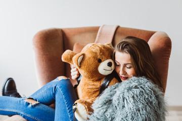 Girl cuddling with teddy bear on sofa
