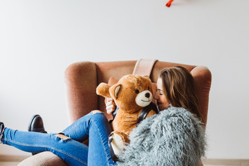 Girl cuddling with teddy bear on sofa