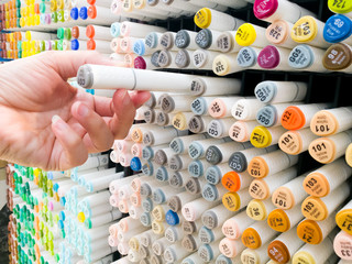 focus on women hand select the color pen on the shelf at stationery shop