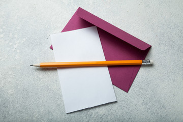 Empty sheet of paper and an envelope with a pencil on a white vintage desk.