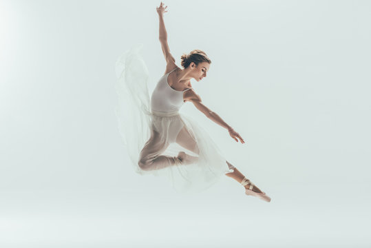 beautiful ballet dancer in white dress jumping in studio, isolated on white