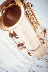 Part of saxophone lying on the notes