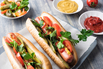 Hot dogs on wooden background. Homemade sandwiches with sausages, tomatos, pickles, mustard and ketchup on plate. Wrapping paper