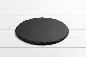 Slate plate on table. black slate stone on wooden background. copy space