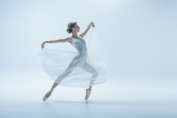 elegant ballerina in white dress dancing in studio, isolated on white