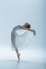 beautiful ballerina dancing in studio, isolated on white