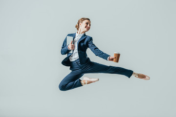 businesswoman in suit and ballet shoes jumping with coffee and digital tablet, isolated on grey Wall mural
