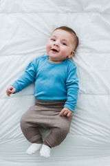 Portrait of an adorable 3 month old baby smiling lying in a bed of white sheets