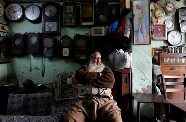 A man sits inside his 42-year old shop of antique clocks in the old quarters of Delhi