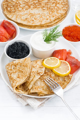 crepes with fish, sour cream and caviar, vertical, top view