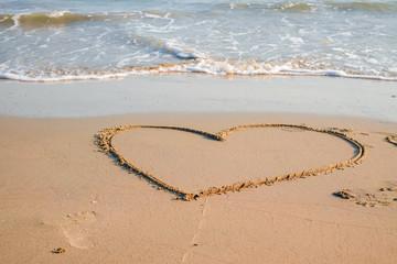 Heart drawn on the sand of a sea beach