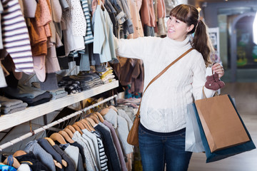 Young pregnant woman choosing clothes for baby