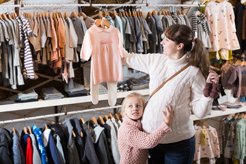 Pregnant female and small daughter choosing clothes