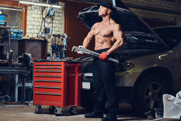 Shirtless mechanic in a garage.