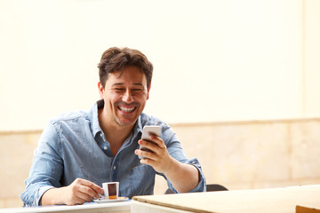 cheerful middle aged guy looking at smart phone and laughing with cup of coffee at cafe