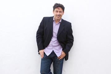 handsome mature businessman posing in stylish jacket against white background
