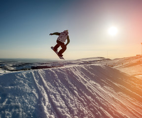 Jumping snowboarder in mountains
