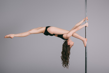 flexible sporty female dancer exercising with pole on grey Wall mural