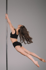 side view of attractive flexible woman dancing with pole on grey