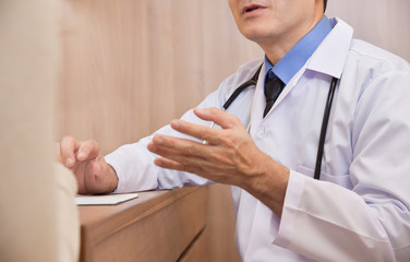 Asian Senior male Doctor talking to female patient.