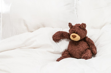 An old, worn teddy bear sat on white sheets on a bed