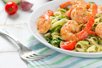 Zucchini noodles sauteed with cherry tomato and prawns close up