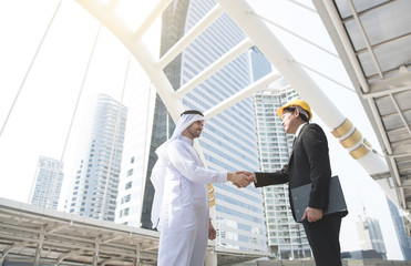 businessman arabic with engineer making handshake agreement. concept finishing up a meeting.