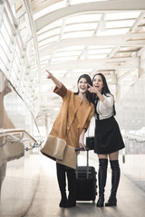Young woman with travel bag pointing finger at the airport for traveler tourism.
