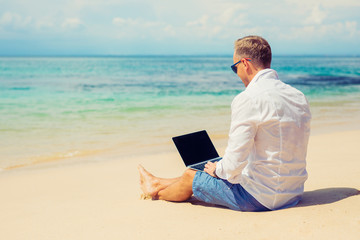 Young businessman using laptop computer on the beach