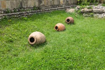 Old clay earthenware pots in a row in a garden.