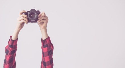Young female, raised up arms and holding camera isolated background