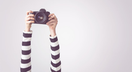 Female arms up, holding camera, isolated background