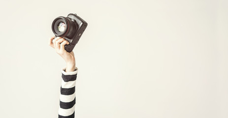 Wall Mural - Young female raised up arm and holding camera