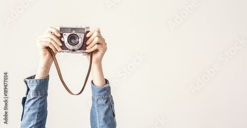 Wall mural Arms up holding vintage camera isolated background