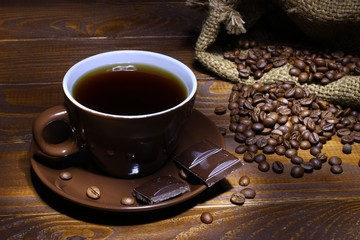 Coffee in a brown pot, coffee beans, chocolate