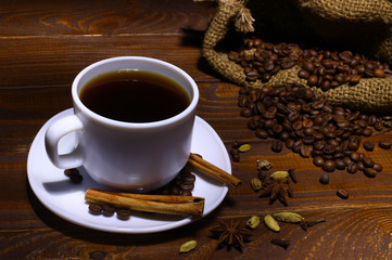 Coffee in a white pot, cinnamon, coffee beans