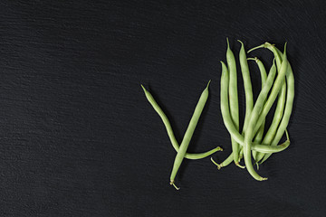 Pods fresh green beans on a black stone surface.  Top view, copy space. Healthy eating concept.